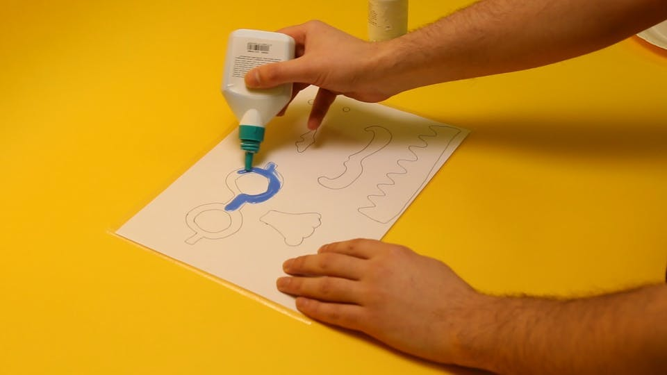 Squeeze the coloured glue over the template or apply it using a paintbrush