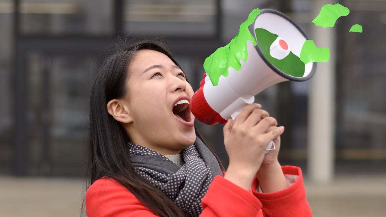 Woman shouting into a slime filled megaphone