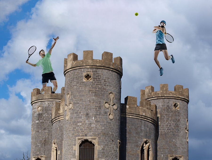 Two people playing tennis on top of a castle!