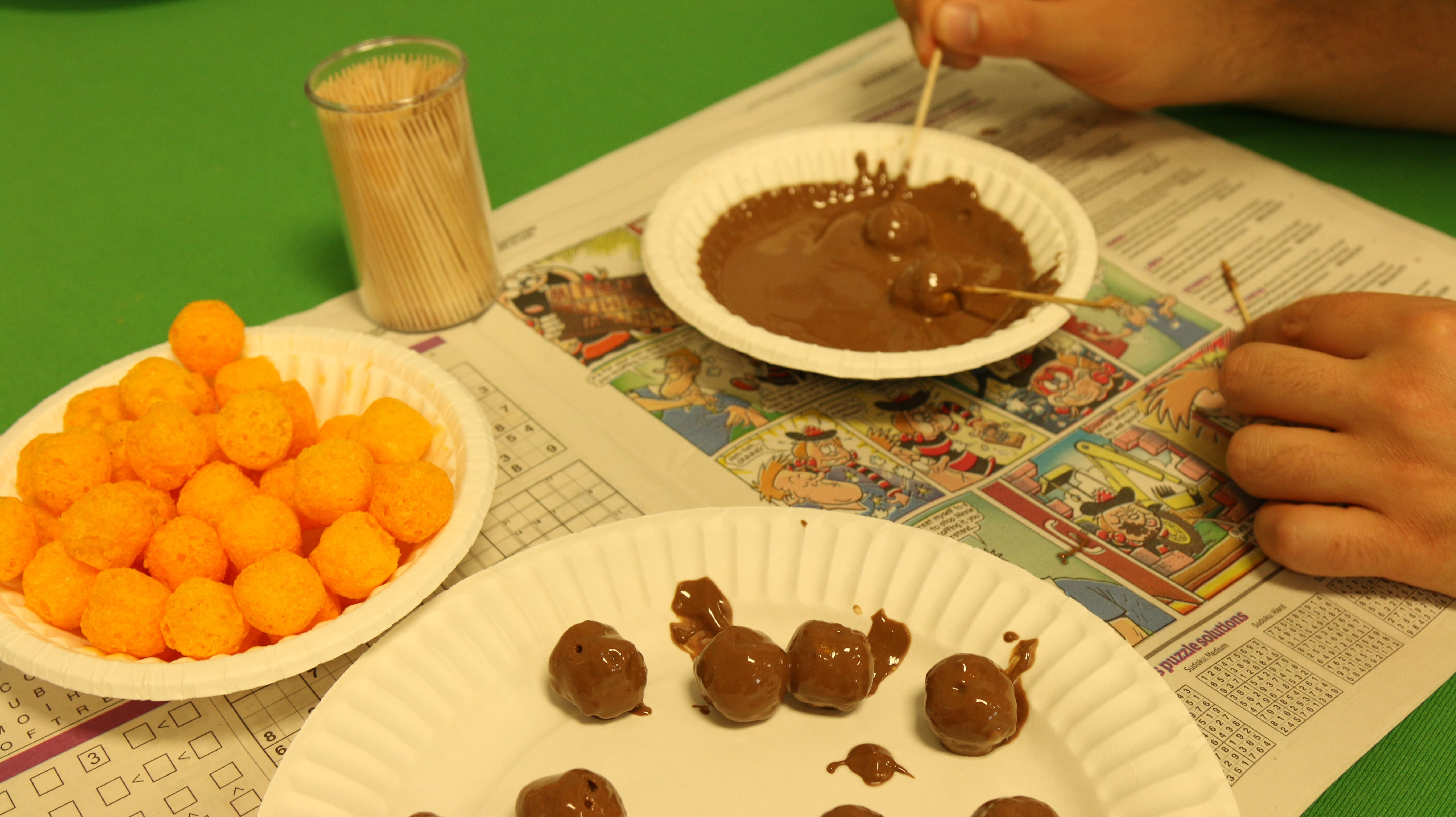 Cover the cheese puffs all over with chocolate, one by one, and let them settle on another plate or tray.