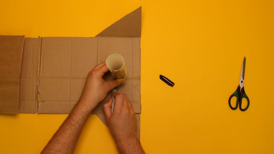 Trace the end of the tube, marking out a circle on the end panel of your cardboard