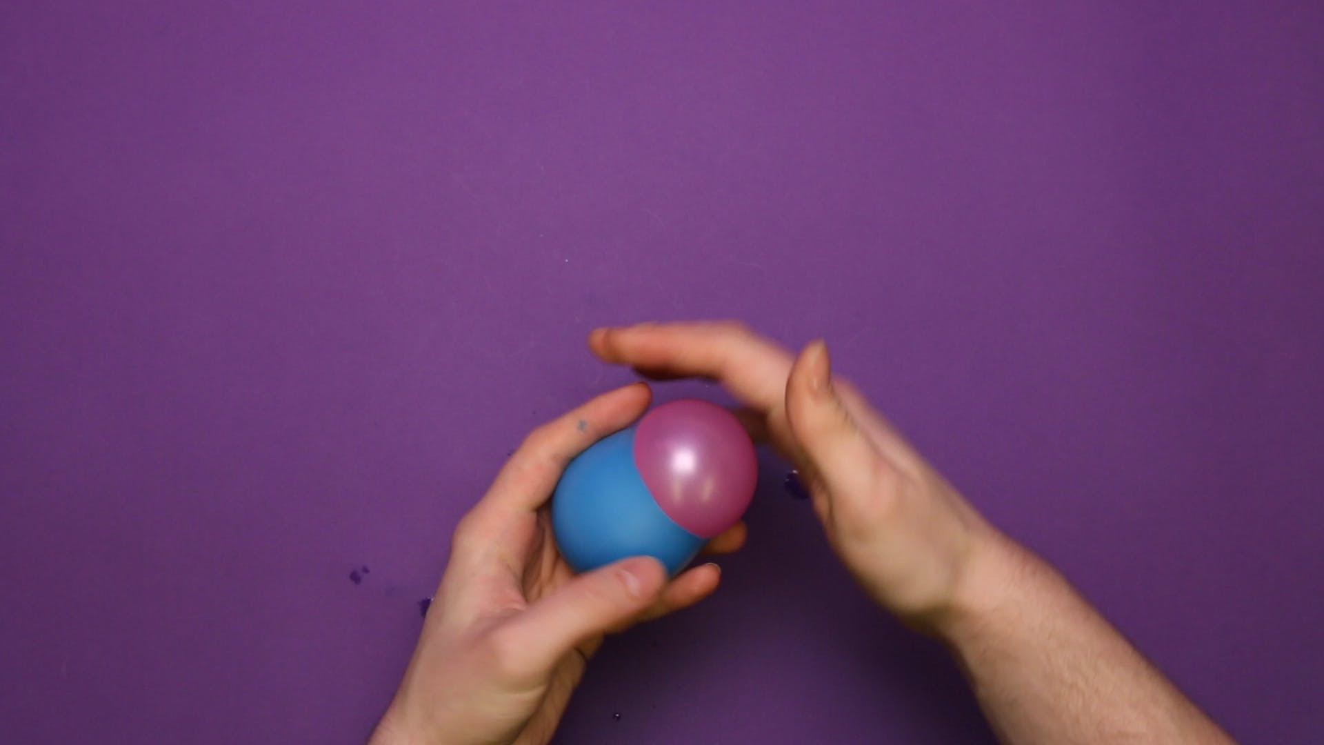 Squeeze the water-filled balloon into the new balloon