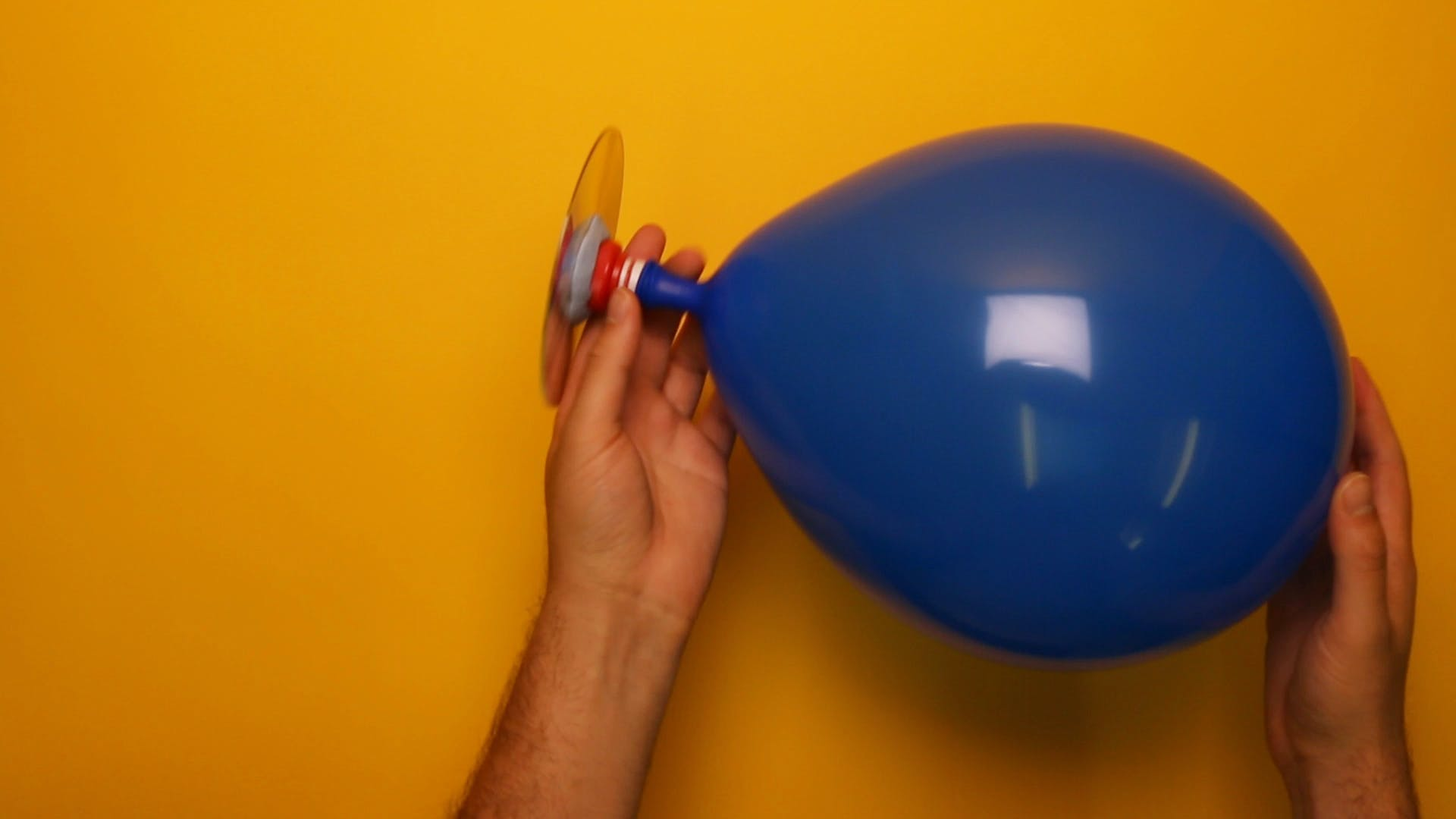 Inflate the balloon by blowing through the hole in the CD. Close the sports cap to keep the air in!