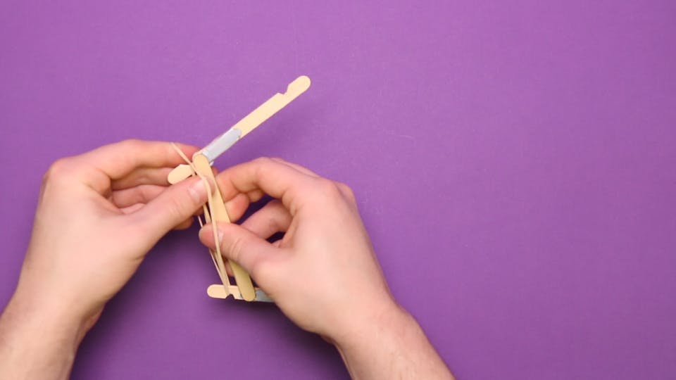 Stretch a rubber band between the 2 notches on the front. Loop it round if you need to make it tighter.